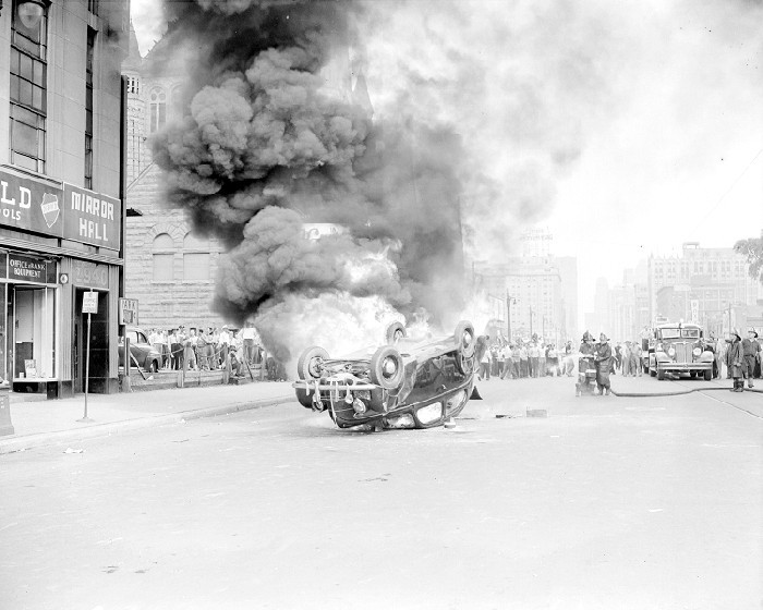 Riots: Detroit: Race Riots, 1943. June 21, 1943. Burning & Wrecked Autos. Rioters Running from Tear Gas. Burning Car on Woodward near Stimpson.